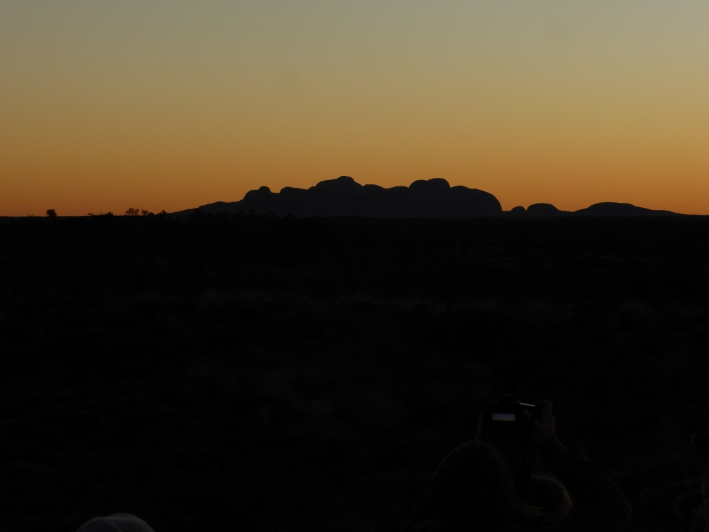 The Olgas. Taken from the back of a Camel, at sunset from a long distance!! Please excuse Nikki for wrecking the photo with her camera lights (she's a few camels in front)....!