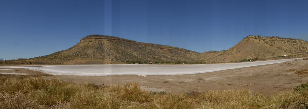 down at the port, looking over a salt pan up at a hill